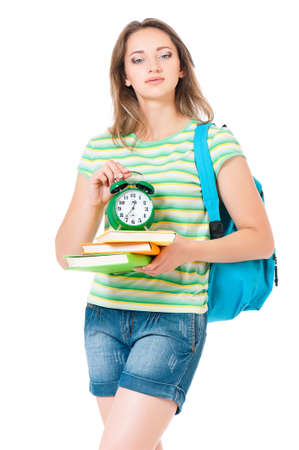 Beautiful student girl with backpack, books and green alarm clock, isolated on white background photo