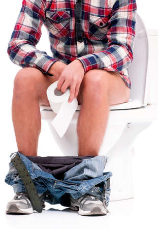 Man is sitting on the toilet bowl, holding paper in hands, on white background photo