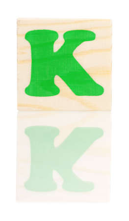Wooden block with letter K, isolated on white background photo