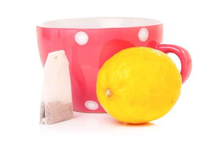 mugged: Big mug polka dot of tea with lemon, isolated on white background