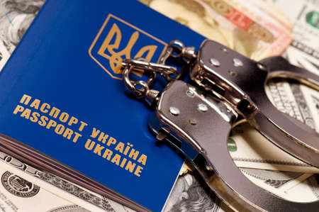 International Ukrainian passport with handcuffs on money background photo