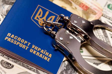International Ukrainian passport with handcuffs on money background photo
