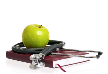 Stethoscope, green  apple and book, isolated on white background photo