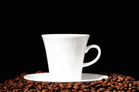 White coffee cup on coffee beans on black background photo