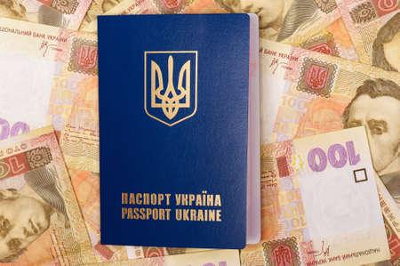 hryvna: International Ukrainian passport on Hryvna banknotes background Stock Photo