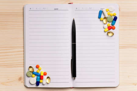 Close up pills and paper on wooden background  photo