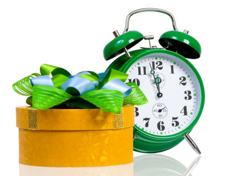 Big green alarm clock with gift box, isolated on white background photo