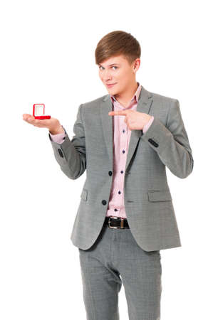 Happy young man holding box with wedding ring, isolated on white background photo
