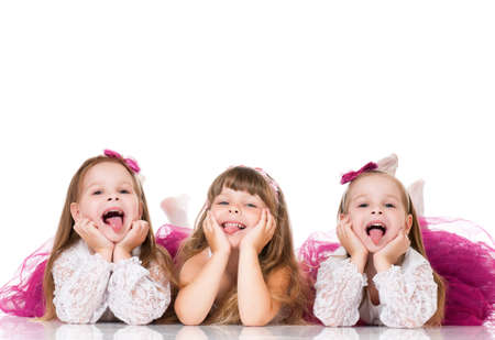 Group of adorable little girls having fun lying on floor, isolated on white background photo