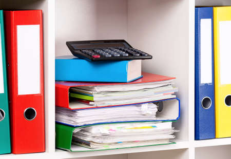 chaos order: File folders and calculator on the shelves at office Stock Photo