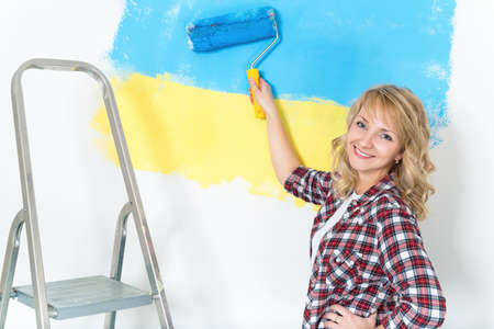 repairs: Happy woman makes repairs at home - painting wall at room. Portrait of smiling woman painting big Ukrainian flag on wall at home. Stock Photo