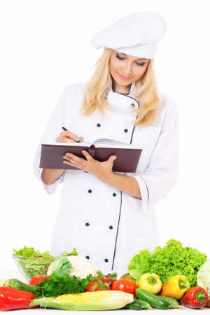 culinary skills: Woman cook in chef hat with fresh vegetables, isolated on white background
