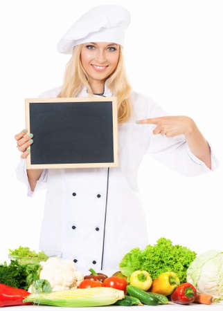 female clothing: Woman cook in chef hat with small blackboard and fresh vegetables, isolated on white background