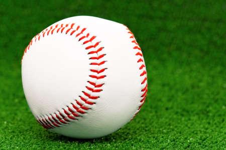 artificial: Single baseball ball on artificial green grass Stock Photo