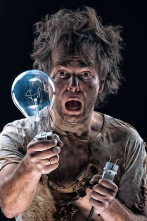 electric bulb: Portrait of burnt man with light bulb and electric plug over black background