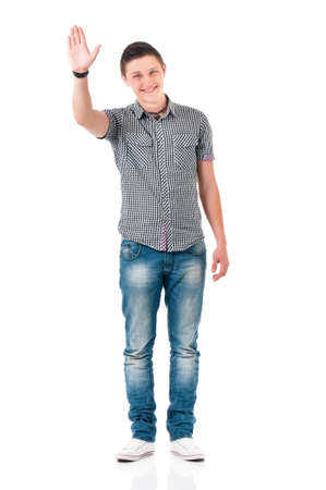 Full length portrait of smiling young man greets with his hand, isolated on white background