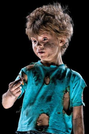 Portrait of burnt little boy with cigarette butt, over black background