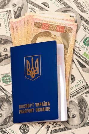 hryvna: International Ukrainian passport with Hryvna banknotes on US dollars background Stock Photo