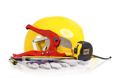 Yellow hard hat with work gloves and tools on a white background
