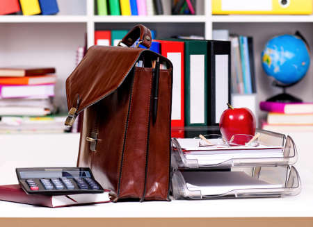 portmanteau: Brown leather briefcase on table at office Stock Photo