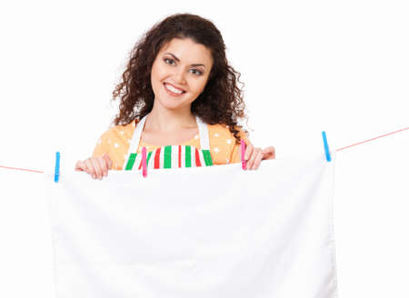 launder: Young housewife hanging clothes on the line, isolated on white background