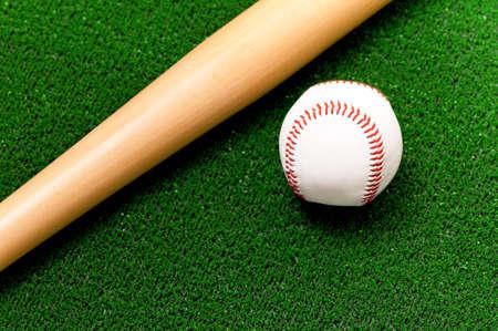 ballpark: Close-up of baseball ball and bat on artificial green grass