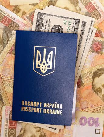hryvna: International Ukrainian passport with US dollars on Hryvna banknotes background