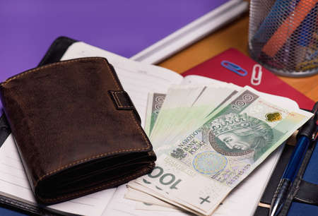 Notepad with purse and Polish money banknotes on table