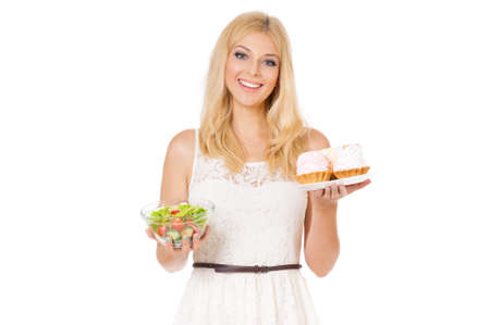 yearning: Half-length portrait of very beautiful woman holding small cake, fresh vegetables. Young housewife choosing sweets or healthy eating - cake and salad. Laughing at camera. Isolated on white background. Stock Photo