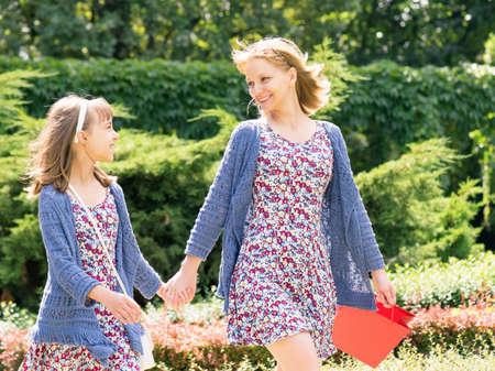 매력적인 미소 어머니와 딸 재미 함께 쇼핑을하는 동안 여행. 아름 다운 행복 한 가족 다채로운 쇼핑백와 산책 하 고 손을 잡고. 같은 드레스 야.