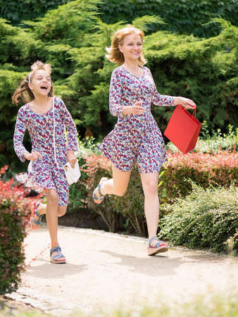 shopping trip: Attractive smiling mother and daughter having fun together during shopping trip. Beautiful cheerful family - mom with her little child - running with colorful shopping bag. The same dress. Stock Photo