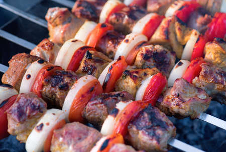 Barbecue with delicious grilled meat on grill. Pork meat pieces being fried on a charcoal grill.