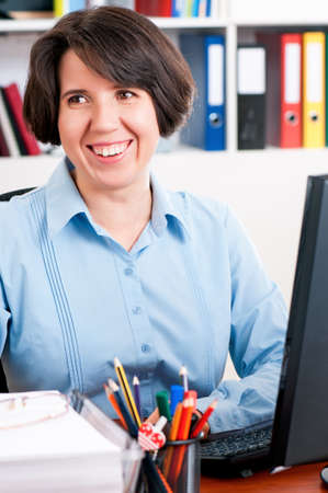 Young woman in office, sitting at desk. Businesswoman working on a desktop computer. Portrait of female at work.