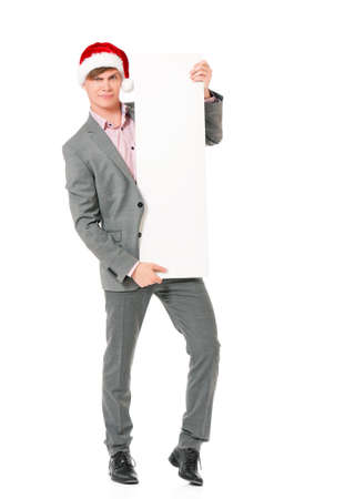 full lenght: Caucasian man wearing christmas hat for santa. Young businessman in gray suit with blank sign isolated on white background. Successful boy wearing Santa Claus hat - full lenght portrait. Stock Photo