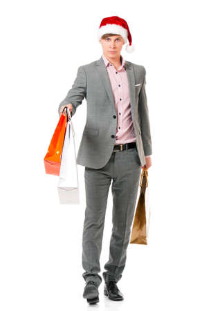 full lenght: Caucasian man wearing christmas hat for santa. Young businessman in gray suit with shopping bags isolated on white background. Successful boy wearing Santa Claus hat - full lenght portrait. Stock Photo