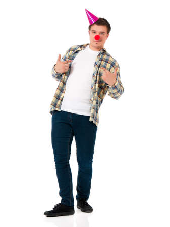 Handsome man clown isolated on white background. Teen boy with crazy look making faces and wearing red nose. Stock Photo