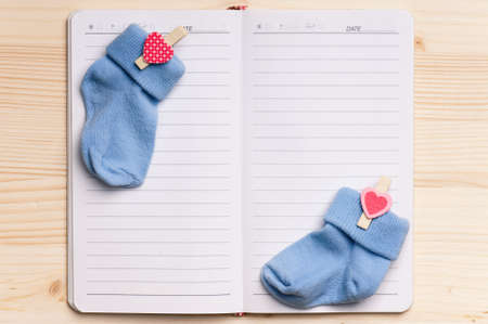 notebook page: Baby shoes and notepad for note on a wooden table. Blank paper - view from above. Stock Photo