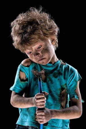 electric shock: El muchacho tiene una descarga eléctrica. Retrato del pequeño electricista divertido con el enchufe del cable sobre el fondo negro. Concepto de la potencia eléctrica.