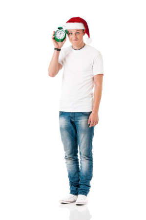 full lenght: Caucasian young man wearing christmas hat for santa. Teenager in white t-shirt with alarm clock isolated on white background. Happy boy wearing Santa Claus hat - full lenght portrait.