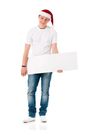 Caucasian man wearing christmas hat for santa. Teenager in white t-shirt with blank sign isolated on white background. Successful boy wearing Santa Claus hat - full lenght portrait.