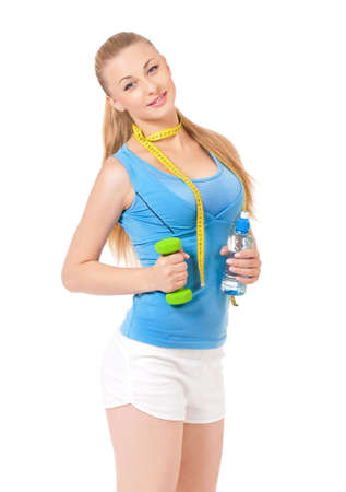 waistline: Young woman doing fitness exercise, isolated on white background. Portrait of beautiful athlete girl with bottle of water, dumbbells and tape measure in studio.