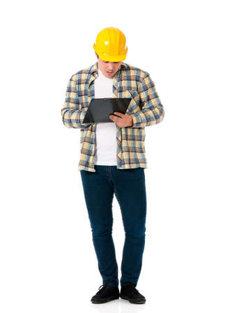 full lenght: Full lenght portrait of a young architect with yellow hard hat. An engineer or foreman holding clipboard. Young construction worker or businessman wearing helmet, isolated on white background.