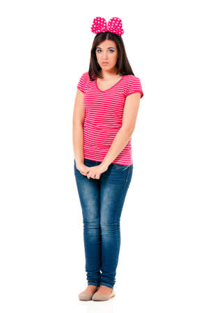 full lenght: Sad teen girl with big red bow, isolated on white background. Expressive full lenght portrait of young brunette woman with shy gesture and posture.