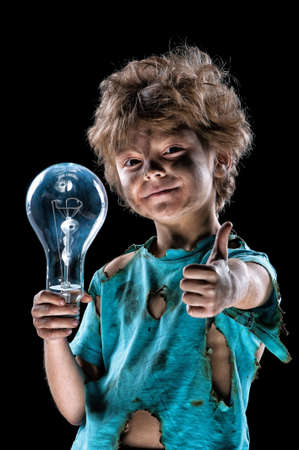 jolt: Boy has a electric shock. Portrait of funny little electrician with light bulb doing a thumb gesture over black background. Electricity power concept.