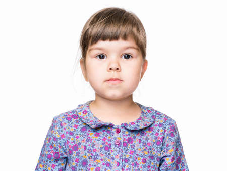 Emotional portrait of a 3 years old girl, serious. Cute caucasian baby isolated on white background. Beautiful preschool child posing in studio. Healthy carefree kid playing indoors.