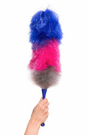 broom handle: Hand holding broom for cleaning or soft colorful duster with plastic handle, isolated on white background. Cleaning woman holding colorful synthetic duster.