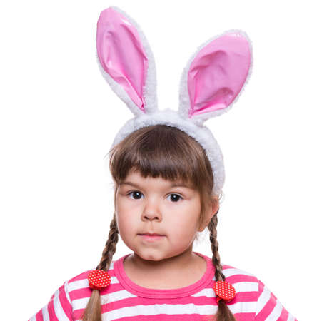 Happy little girl with pink rabbit ears. Portrait of cute caucasian baby wearing bunny ears. Funny preschool child, isolated on white background. Healthy carefree kid - Easter holidays concepts. Stock Photo