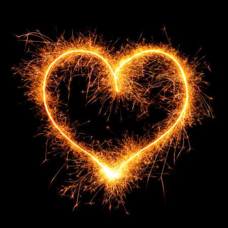 黒い背景に線香花火から心。結婚式や聖バレンタイン カードのデザイン要素です。遅いシャッター スピードでカメラを使用して - ベンガルの火から