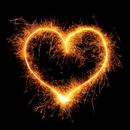 Heart from sparkler on black background. Design element for wedding or Saint Valentine card. Love symbol Valentines Day from bengal fire - using camera with slow shutter speed.