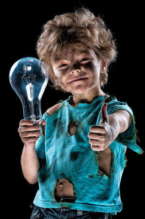 Boy has a electric shock. Portrait of funny little electrician with light bulb doing a thumb gesture over black background. Electricity power concept.